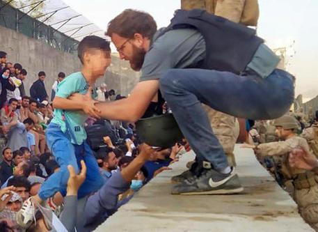 Il console italiano aiuta un bimbo nello scalo di Kabul, la foto è virale